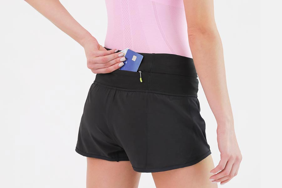 inserting money into secure pocket of Flipbelt running shorts